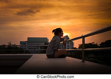 young women looking at the sunset in the lonely and sad concept