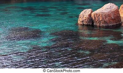Sea, boulder on shore in water