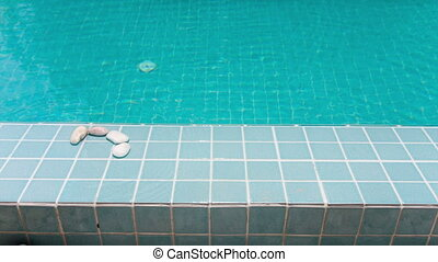 "The inscription ""pool"" is laid out by pebble on a pool..."