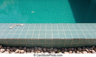 "The inscription "" swim "" is laid out by pebble on a pool..."