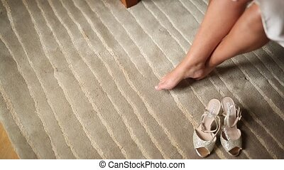 Women's bare legs and shoes near them on the carpet. Wedding in
