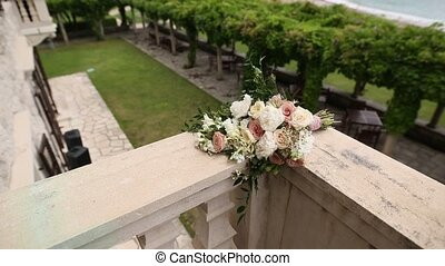 Bouquet of roses and peonies lies on the balcony of the...