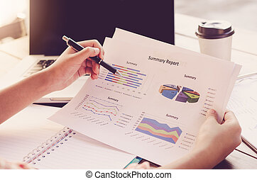 Businessman holding paperwork on the table and analyzing investment chart working in office. Business work concept
