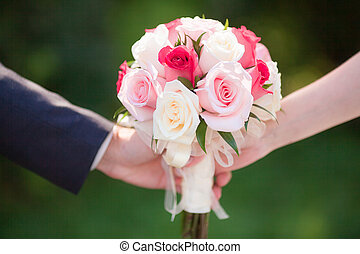 Beautiful pink wedding bouquet in hands of bride and groom