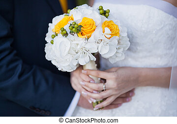 Beautiful yellow wedding bouquet in hands of bride and groom