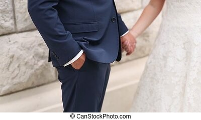 The newlyweds hold hands. Couple holding hands. Wedding in...