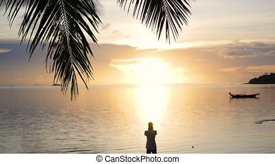 The guy takes a picture of the sunset panorama on the beach....