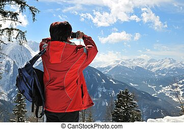 Senior woman taking picture in winter mountains - Senior...