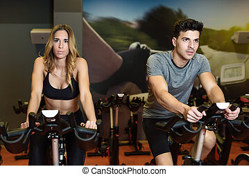 Couple in a spinning class wearing sportswear. - Two people...