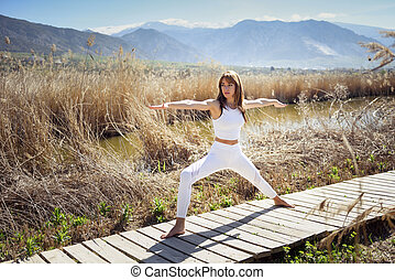 Young woman doing yoga in the beach. Female wearing white...