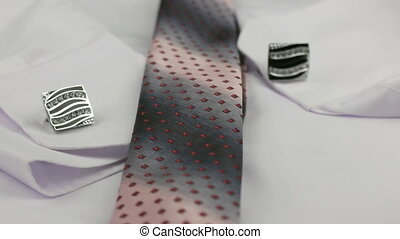 Red tie and cufflink on a white shirt, close-up. Dolly shot....