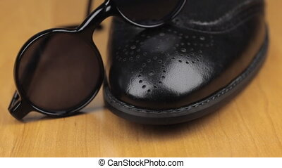 Black sunglasses are on black men's shoes. Dolly shot....