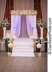 Wedding ceremony hall ready for guests,Luxury, elegant wedding reception table arrangement,Indoors wedding reception venue with decor,Beautiful wedding ceremony design decoration elements with arch