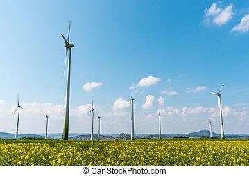 Wind farm in a blooming rapeseed field seen in Germany