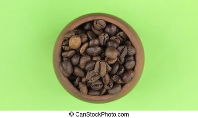 Rotation of the bean of coffee in a pot isolated on green...