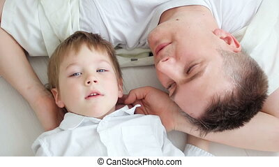 father with son at home lying on the floor