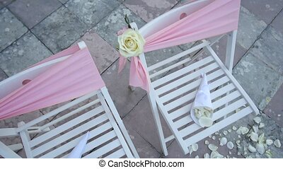 Chairs at a wedding ceremony. Decorated with flower arrangements