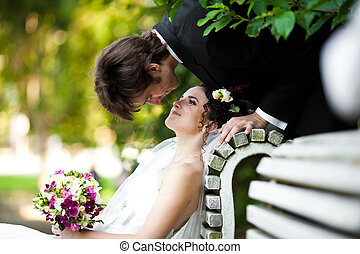 Bride admires a groom while he bends over her