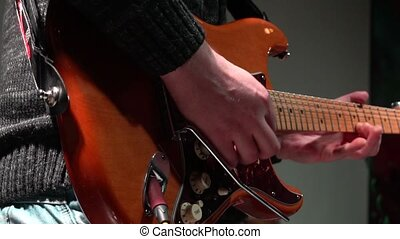 The man is masterly playing an electric guitar at a rock concert. close-up. In slow motion.