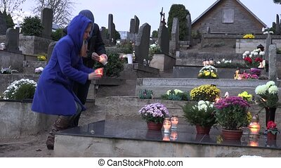 couple burn candle on black marble tomb grave in cemetery....