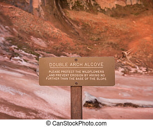 Double Arch Alcove Sign cautions tourists to protect the...