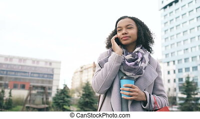 Attractive mixed race girl talking smartphone and drinking coffee in city street with bags. Young woman after shopping on mall sale