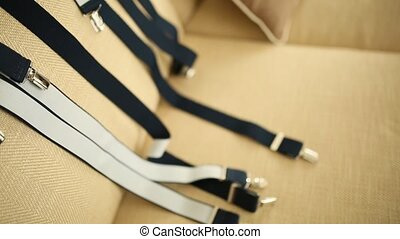 men's suspenders lying on the couch
