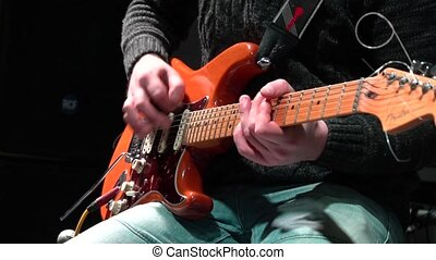 The man is masterly playing an electric guitar at a rock concert. close-up.
