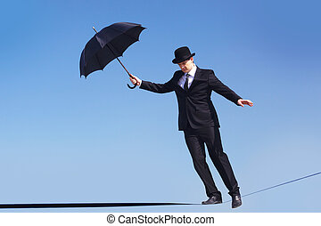 Balancing - Photo of skilled businessman with open umbrella...