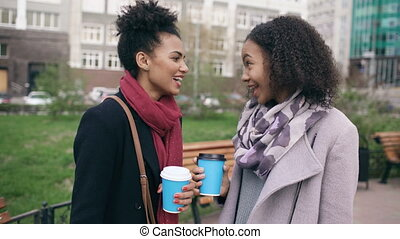 Two attractive mixed race women with shopping bags drinking coffe and talking at the street. Young girls smiling and have friends conversation