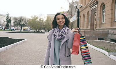 Dolly shot of Attractive mixed race girl walking towards with shopping bags and smiling into camera. Happy young woman walking after visiting mall sales