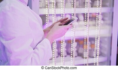 Side view of woman s hands in a lab coat texting