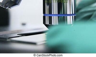 Scientist putting liquid under microscope, close up -...