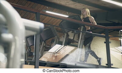 A beautiful blonde quickly runs down the treadmill in the...
