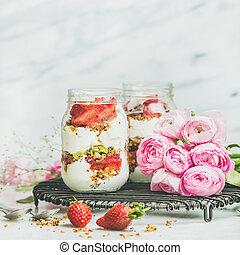 Healthy spring breakfast jars with pink raninkulus flowers,...