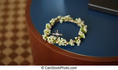 Wreath of small white flowers on the table. Wedding crown of...