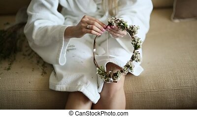 The bride in a white hotel gown wove wreath gypsophila - The...