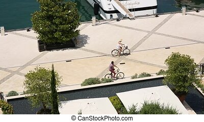 Cyclists ride bicycles by the marina for yachts. District...