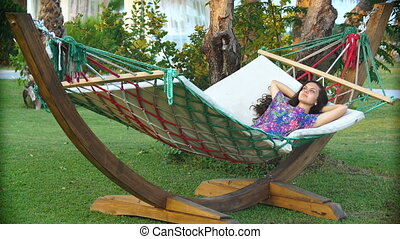 smiling brunette woman in hat relaxed in the hammock on tropical beach