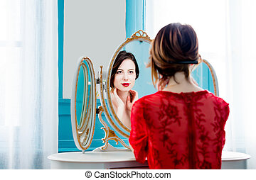 young woman looking at mirror - portrait of beautiful young...