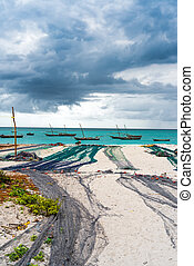 view of large fishing nets on a seashore with ocean and boats on the background