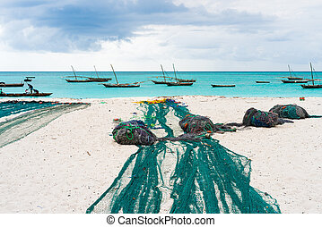 large fishing nets lying on african beach with boats near the shore