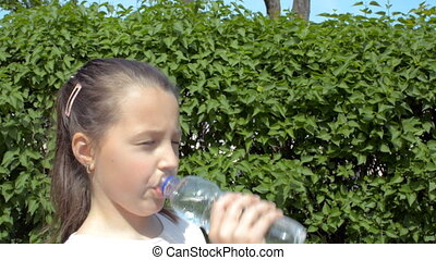A girl drinks water from a plastic bottle against a background of green bushes.