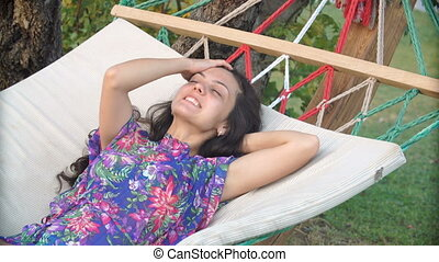 smiling brunette woman in hat relaxed and dreaming in the hammock on tropical beach