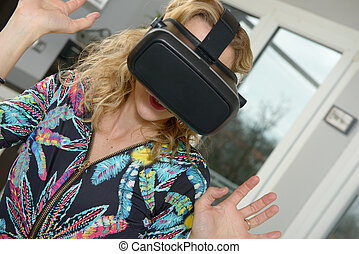 pretty young woman using virtual reality device - pretty...