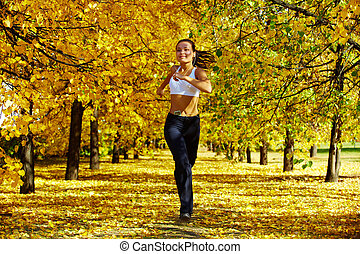 Autumn fitness - A young girl jogging among golden autumn...