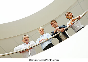 Team - Business team with smiles leaned on the handrail