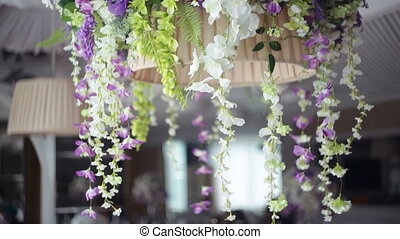 Wedding decor of flowers on a chandelier in a restaurant.