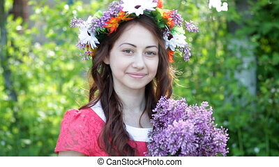 Beautiful young woman with a wreath on her head and a bouquet of lilac in her hands