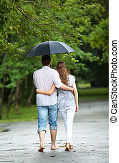 Walking in the rain - Rear view of a couple walking in the...